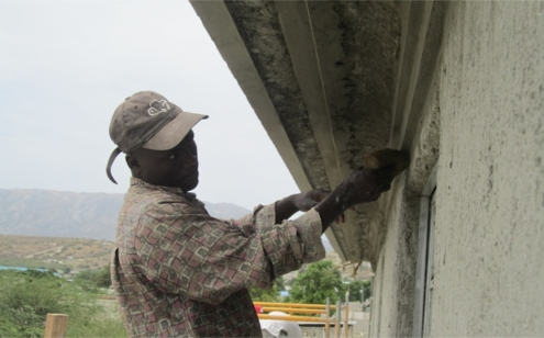 Plasterer Completing Molding on Orphanage.